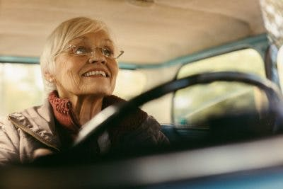 close up of elderly woman behind the wheel, smiling because she can drive again after a stroke