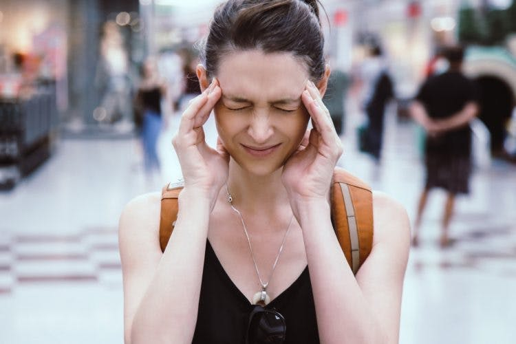 woman rubbing sides of her head to relieve headaches after brain injury