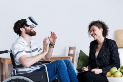 man in wheelchair using virtual reality system while smiling therapist watches and takes notes