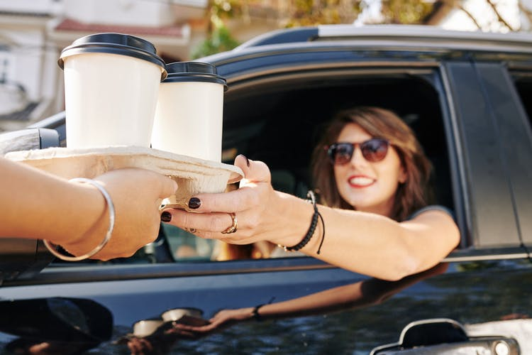 woman in car reaching for to-go coffee cups in drive-thru window because she needs caffeine after brain injury