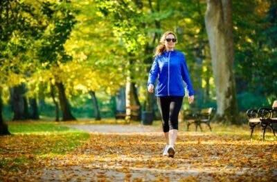 woman walking through park as an alternative to caffeine after brain injury