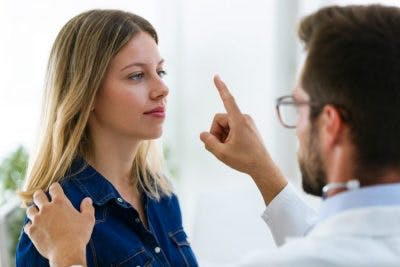 doctor holding finger up in front of woman's eyes to check if vision problems are causing her dizziness after head injury