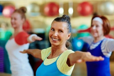 senior woman practicing balance exercises in exercise class