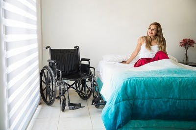 woman with spinal cord injury practicing bed mobility exercises