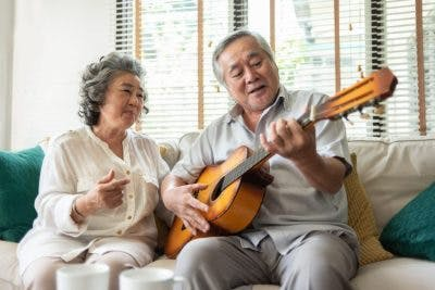 elderly couple singing and playing guitar on couch