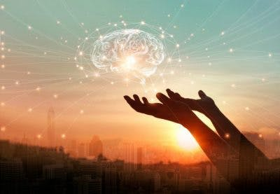hands holding hologram of brain in front of sunset