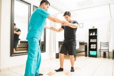 therapist teaching patient how to walk after cerebellum brain damage