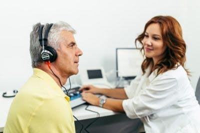 man wearing headphones taking a hearing test to determine whether he has sensorineural hearing loss after head injury