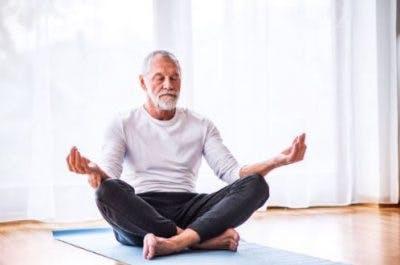 senior man practicing meditation in living room on yoga mat