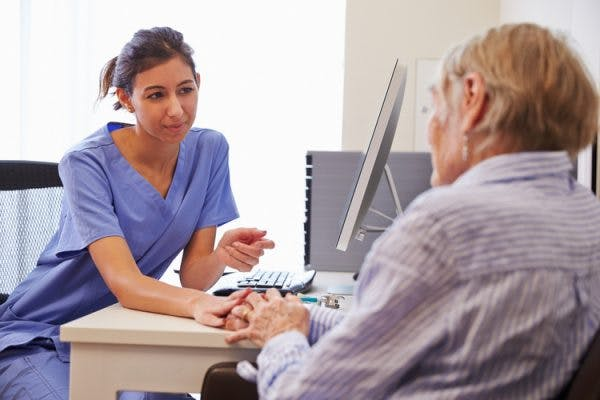 elderly patient in doctor's office discussing transcortical motor aphasia with doctor