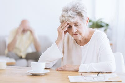 elderly woman sitting at kitchen table looking stressed because she has transcortical sensory aphasia