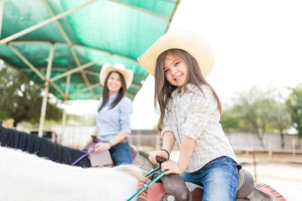 little girl with cerebral palsy participating in hippotherapy to improve trunk stability