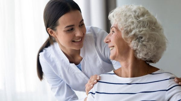 nurse helping elderly patient with global aphasia