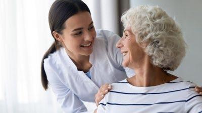 doctor putting hands on elderly patient's shoulders