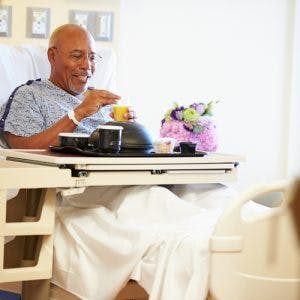 man in hospital bed with tray of food catered for dysphagia after brain injury