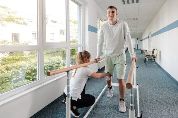 young man working on physical therapy for spinal cord injury treatment
