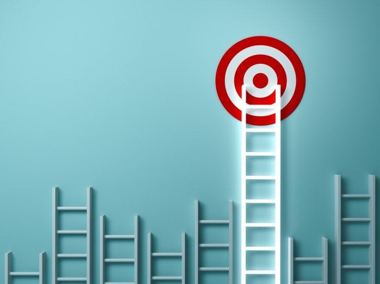 a ladder leaning up against a wall with the top reaching a target on the wall to illustrate accomplishing goals after stroke