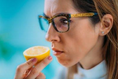 woman sniffing orange slice