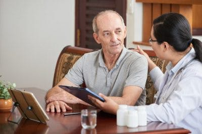 doctor sitting at patient's dining room table teaching him how to manage primary progressive aphasia