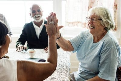 senior woman giving friend a high five because she recovered from anomic aphasia