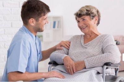therapist helping stroke patient in wheelchair