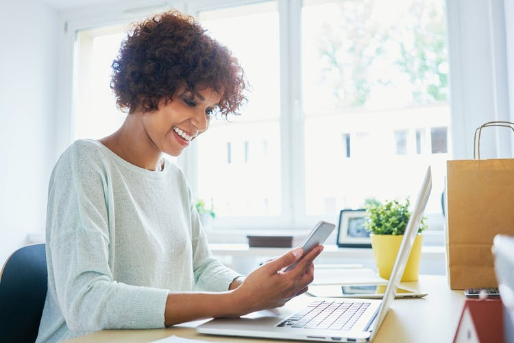 woman smiling while looking at computer researching disability benefits after stroke