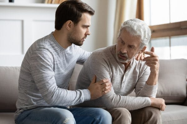 adult son trying to help elderly father cope with anger after stroke