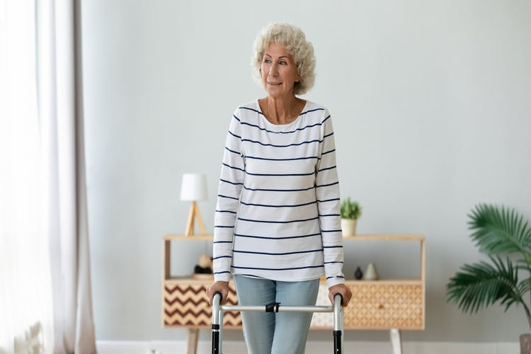 smiling older woman using walker to help reduce dizziness after stroke