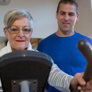 therapist instructing stroke patient on how to use an exercise bike to overcome chronic stroke