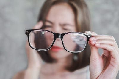 woman squinting and holding pair of glasses to represent vision problems that can impair driving after brain injury