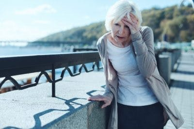 senior woman leaning on rail because she is experiencing dizziness after stroke