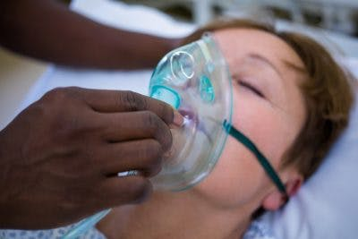 Nurse placing an oxygen mask on the face of a global brain injury patient in hospital