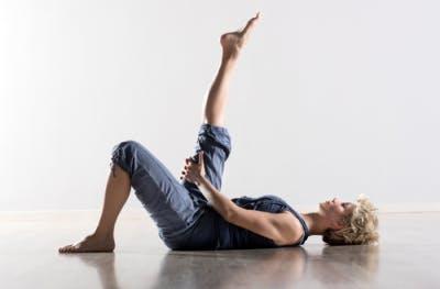 Mujer tendida en el suelo estirando las piernas para fisioterapia en casa