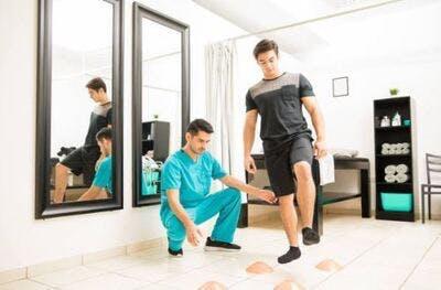 Physiothérapeute en gommages aidant le patient à marcher dans un exercice d'équilibre