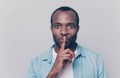 Hombre haciendo la señal de silencio durante la fisioterapia en casa