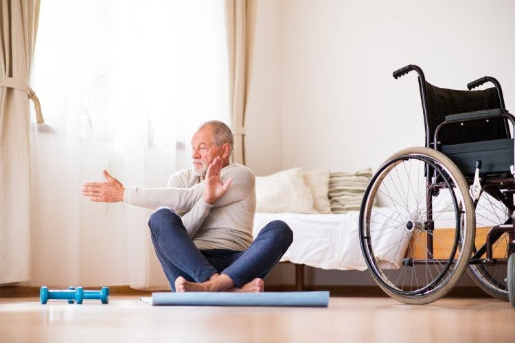 Adulto mayor paciente con accidente cerebrovascular sentado en un tapete de yoga haciendo estiramientos de fisioterapia con el brazo