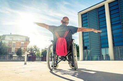 Hombre en silla de ruedas con los brazos extendidos mostrando actitud positiva