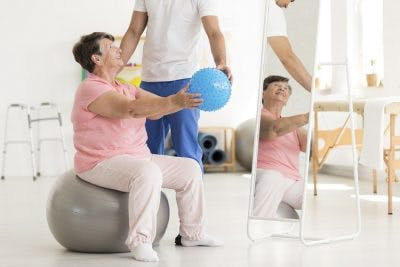 stroke patient sitting on balance ball during physical therapy session