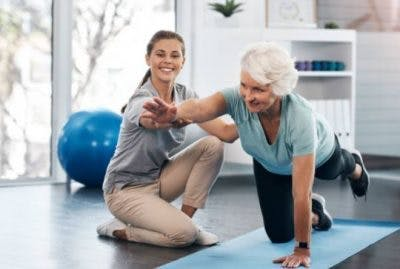 therapist assisting stroke patient with floor exercises that will help her recover from chronic stroke effects