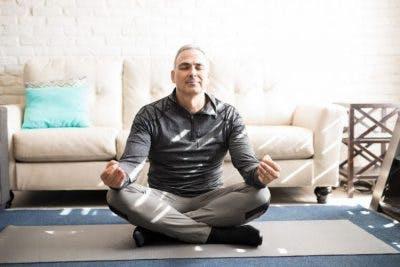 senior man sitting on floor in living room, meditating