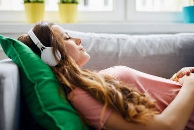 woman lying on couch closing her eyes while wearing headphones