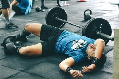 man lying on the gym floor looking exhausted from overworking himself