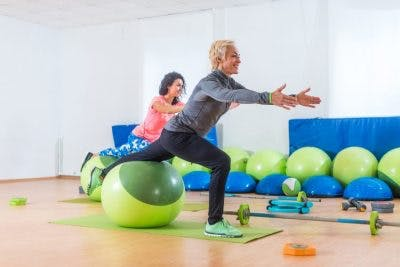 woman balancing on exercise ball in gym as part of her vestibular therapy to reduce dizziness
