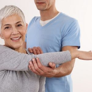 physiotherapist helping a stroke survivor with arm mobility after her symptoms started getting worse
