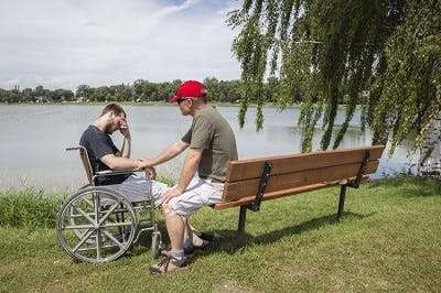 father helping son manage depression after spinal cord injury