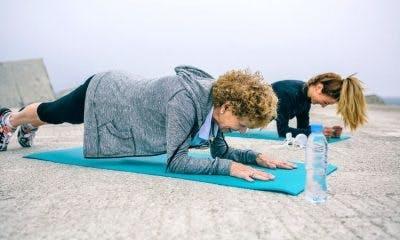 Patient et thérapeute faisant des exercices de planche sur un tapis de yoga