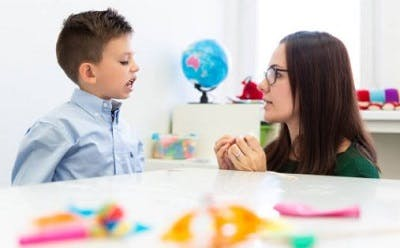 child with cp working with a speech language pathologist to strengthen oral muscles