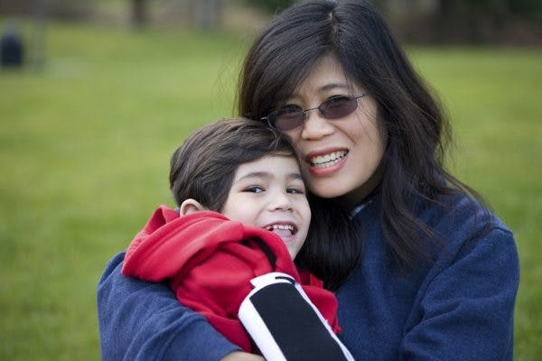 mother hugging son with acquired cerebral palsy