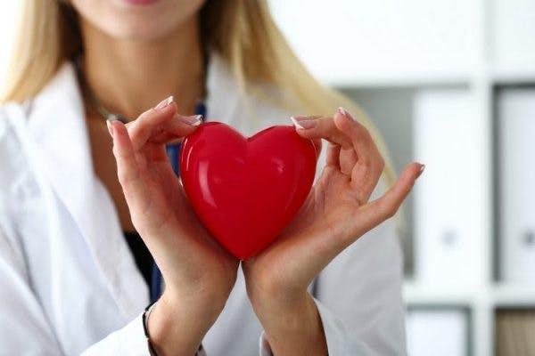 médecin tenant un coeur rouge entre ses mains pour symboliser la récupération de la main