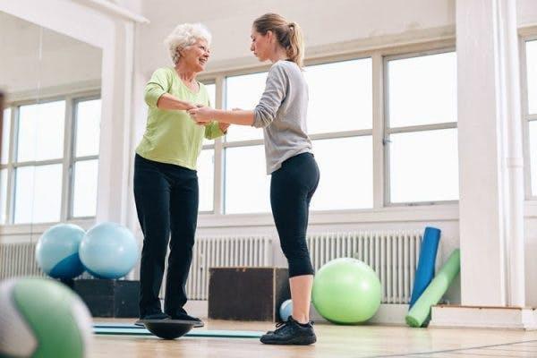 Terapeuta ayuda a equilibrar a paciente con accidente cerebrovascular durante la rehabilitación hospitalaria